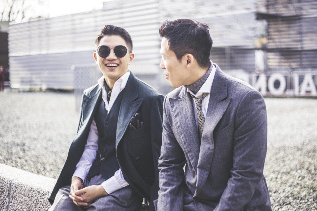 Dva muži v obleku sedící na slavném Pitti chodníku.