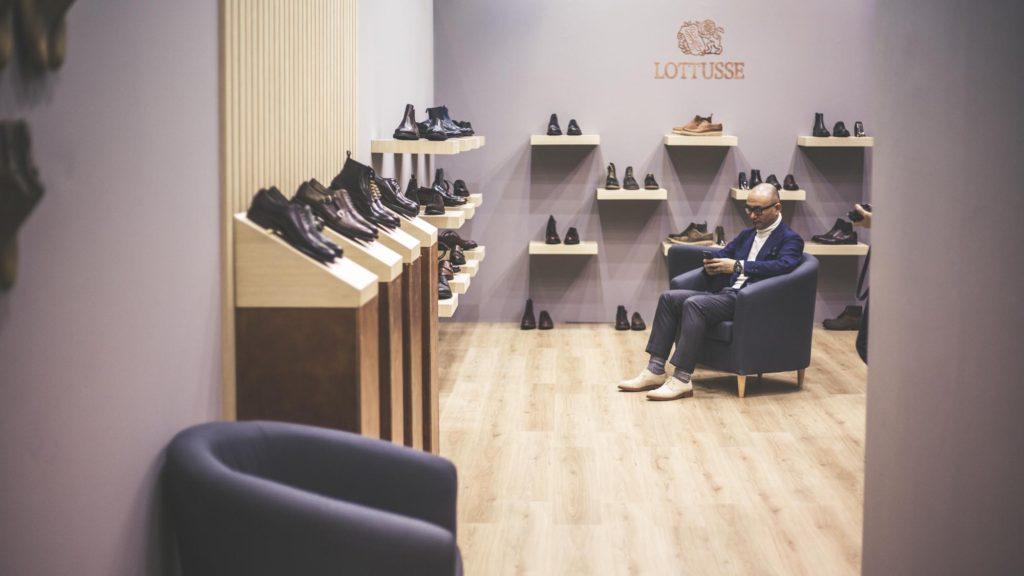 Muž sedící mezi botami v hlavní budově s prodejci.