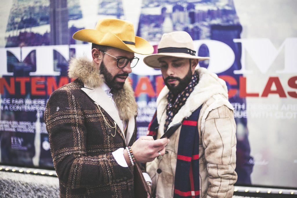 Dva muži v kabátech před velkým Pitti posterem v hlavním prostoru veletrhu.