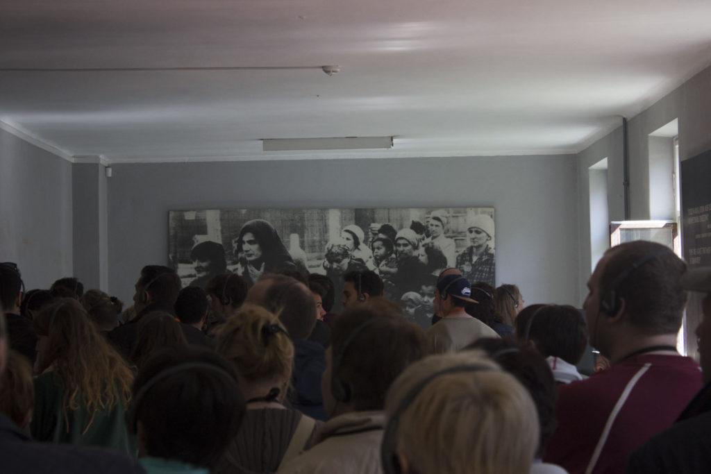 Dav turistů v místnosti v fotografií na zdi